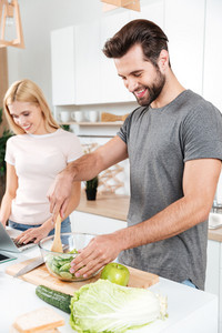 Photo of smiling young loving couple standing at kitchen and cooking together using laptop computer. Looking aside.