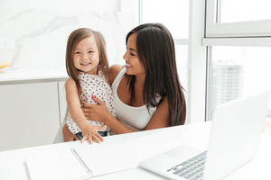 Photo of smiling young mom sitting at the table with little cute asian girl at home indoors using laptop computer writing notes to notebook.