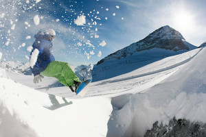 Photo of snowboarder over snowdrift going in for sport in winter