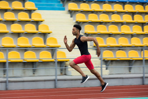 Photo of young african athlete man run on running track outdoors. Looking aside.