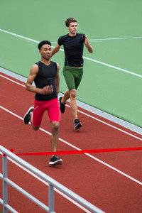 Photo of young group of athlete men run on running track outdoors. Looking aside.