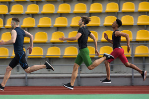 Photo of young multiethnic athlete group run on running track outdoors. Looking aside.