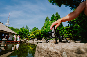 Photograph male hand handling an old vintage camera on tripod in front of water pond film wedding event in known landmark japanese house in Planten un Blomen Park Hamburg, Germany
