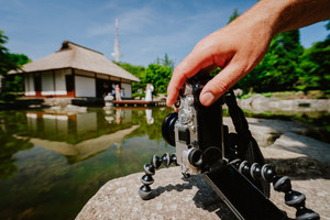 Photograph male hand handling an old vintage camera on tripod in front of water pond with landmark japanese house and wedding couple in Planten un Blomen Park Hamburg, Germany