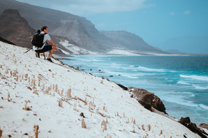 Photographer with camera enjoying quaint moment in scenic coastal landscape of sand dunes and volcanic cliffs. Baia Das Gatas, near Calhau, Sao Vicente Island Cape Verde