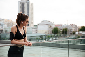 Picture of amazing young sports lady standing with earphones outdoors and looking aside.