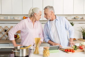 Picture of angry mature man standing near mature serious woman at the kitchen. Looking at each other.