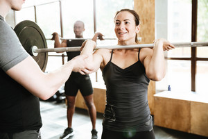 Picture of caucasian strong woman make sport exercise with barbell with trainer.