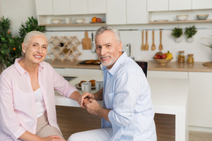 Picture of cheerful mature loving couple family sitting at the kitchen. Looking at camera.
