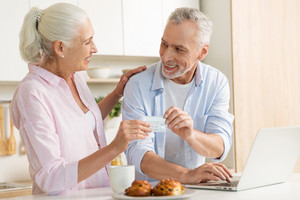 Picture of cheerful mature loving couple family standing at the kitchen using laptop computer holding credit card. Looking at each other.