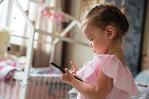 Picture of concentrated little girl child indoors using mobile phone. Looking aside.