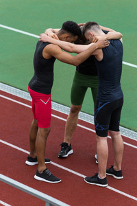 Picture of concentrated multiethnic athlete team standing on running track outdoors. Looking aside.