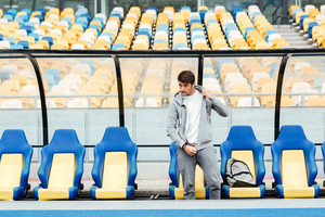 Picture of concentrated young sports man at the stadium outdoors listening music and looking aside.