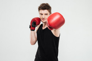 Picture of concentrated young sportsman boxer standing isolated over white background. Looking at camera.