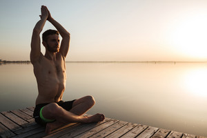 Picture of concentrated young sportsman make yoga meditation exercises at the beach.