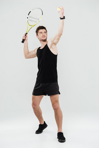 Picture of concentrated young sportsman playing tennis isolated over white background.