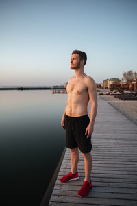 Picture of concentrated young sportsman standing at the beach. Looking aside.