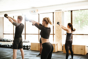 Picture of fitness group of people make sports exercise with weight indoors.