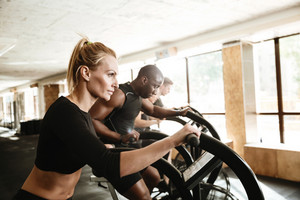 Picture of group of multiethnic sports strong people make sport exercise with spinning bicycles.
