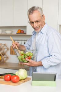 Picture of handsome mature man standing at the kitchen cooking salad. Using tablet computer.