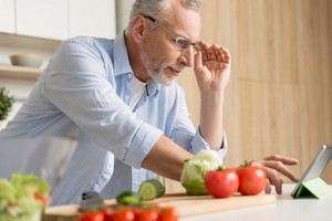 Picture of handsome mature man wearing glasses standing at the kitchen cooking salad using tablet. Looking aside.