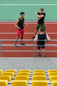 Picture of handsome multiethnic athlete group make stretching exercises on running track outdoors. Looking aside.