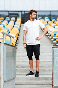 Picture of handsome young sports man at the stadium outdoors listening music and looking aside.