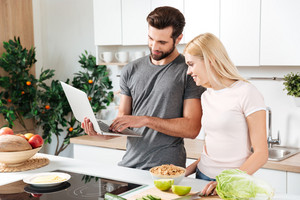 Picture of happy young loving couple standing at kitchen and cooking together using laptop computer. Looking aside.