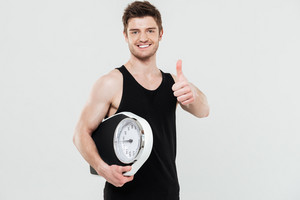 Picture of happy young sportsman holding scales isolated over white background. Looking at camera showing thumbs up.