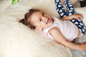 Picture of little cute child girl lies on bed indoors. Looking at camera.