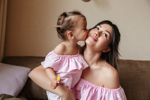 Picture of little girl kissing cheek of her young mother sitting on sofa indoors. Looking aside.