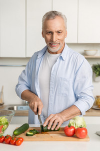 Picture of mature attractive man standing at the kitchen cooking salad. Looking at camera.