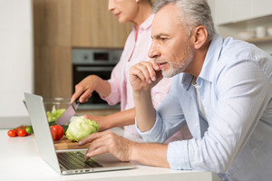 Picture of mature loving couple family standing at the kitchen using laptop computer and cooking salad. Looking aside.