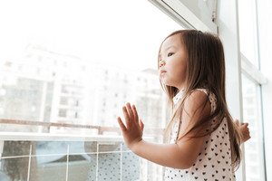 Picture of pretty little cute asian girl at home indoors standing near window. Looking aside.