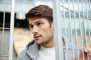 Picture of serious young sports man at the stadium outdoors and looking aside.