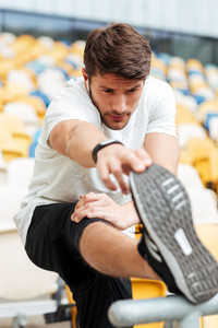 Picture of serious young sports man at the stadium outdoors listening music and looking aside while make stretching exercises.
