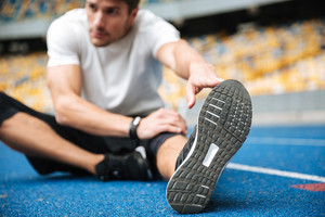 Picture of serious young sports man at the stadium outdoors make stretching exercises.