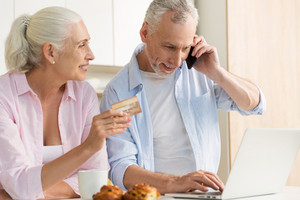 Picture of smiling mature loving couple family standing at the kitchen using laptop computer holding credit card. Looking aside talking by phone.