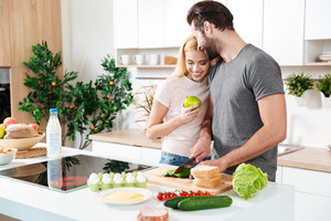 Picture of smiling young loving couple standing at kitchen and cooking together. Looking aside.