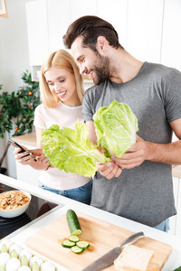 Picture of smiling young loving couple standing at kitchen and cooking together using mobile phone. Looking aside.