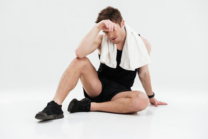 Picture of tired young sportsman with towel sitting on floor isolated over white background.