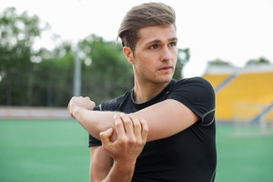 Picture of young concentrated male athlete make stretching exercises outdoors. Looking aside.