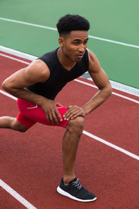 Picture of young handsome concentrated african athlete man make stretching exercises on running track outdoors. Looking aside.