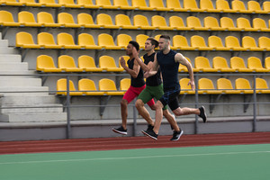 Picture of young multiethnic athlete group run on running track outdoors. Looking aside.