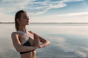 Picture of young sports beautiful woman at the beach make meditation exercises.