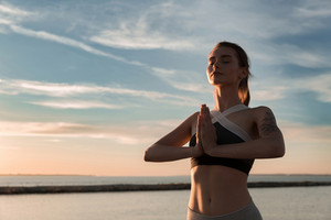 Picture of young sports lady at the beach make meditate exercises.