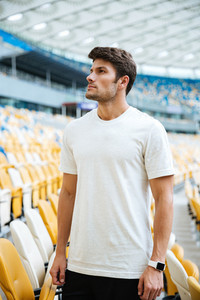 Picture of young sports man standing at the stadium outdoors and looking aside.
