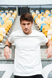Picture of young sports man standing at the stadium outdoors and looking camera.