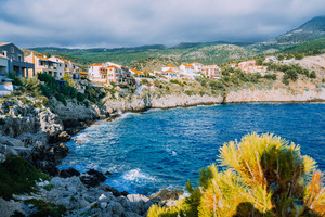 Picturesque coastline in Assos village, Kefalonia island Greece. Colorful houses nestled into the cliff. Summer vacation
