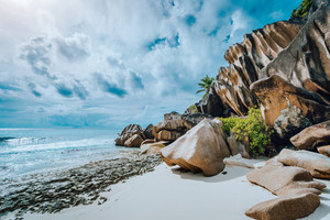 Picturesque granite boulders formation on tropical white sand beach Grand Anse, La Digue island, Seychelles